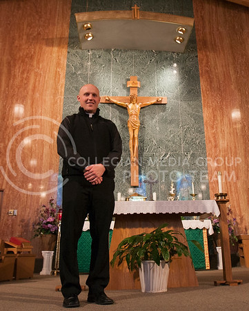 Priest Jarett Konrade stands in front of the chapel of St. Isidore Tuesday afternoon. Konrade takes over the position after Rev. Keith Weber, priest from July 1997 through September 2012, was transfered to the Immaculate Heart of Mary Parish in Salina.  (Photo by Evert Nelson/Collegian)