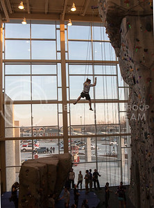 Alex Ondracek, junior studying biology and pre-med, dangles off the new rock wall in the Rec Center Tuesday night. The rec center recently opened its new South end additions.  (Photo by Evert Nelson / Collegian)