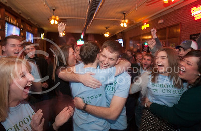Eli Schooley celebrates by hugging his running mate Jake Unruh after hearing the news of winning the SGA elections Wednesday night at Johnny Kaw's. The bar, packed with supporters, erupted after the results were announced on 91.9 The Wildcat.  (Photo by Evert Nelson | Collegian)