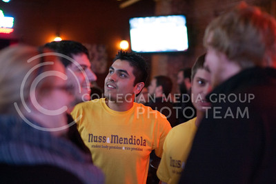 Ariel Mendiola, vice presidental candidate, takes a minute to look at a tv in Johnny Kaw's Tuesday while talking to his running mate Kyle Nuss, presidental candidate, Blair Welin, and Brandon Painter. Welin and Painter walked over to the bar after the hearing the election results from their watch party at Varsity Donuts.  (Photo by Evert Nelson | Collegian)