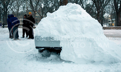 A group of students talk to the side of a snow covered car off Manhattan Avenue Thursday afternoon.  (Photo by Evert Nelson | Collegian)