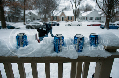 Beers sit in snow on a porch of Manhattan residents Thursday afternoon as students work on a sled ramp in their front yard. K-States campus was closed Thursday due to a snow storm which covered Manhattan with snow.  (Photo by Evert Nelson | Collegian)