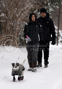 Walter Dodds and Dolly Gutter, Manhattan residents, walk their dog Popper down an alley Thursday afternoon. After a snow storm the night before, the town was covered in a thick blanket of snow.  (Photo by Evert Nelson | Collegian)