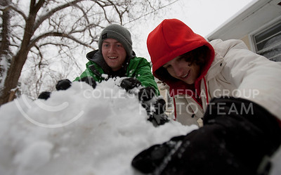 Derek Glover, sophomore studying industrial engineering, packs snow with Corbin Moore, sophomore studying industrial engineering, Thursday afternoon while they make a fort in a friends yard.  (Photo by Evert Nelson | Collegian)