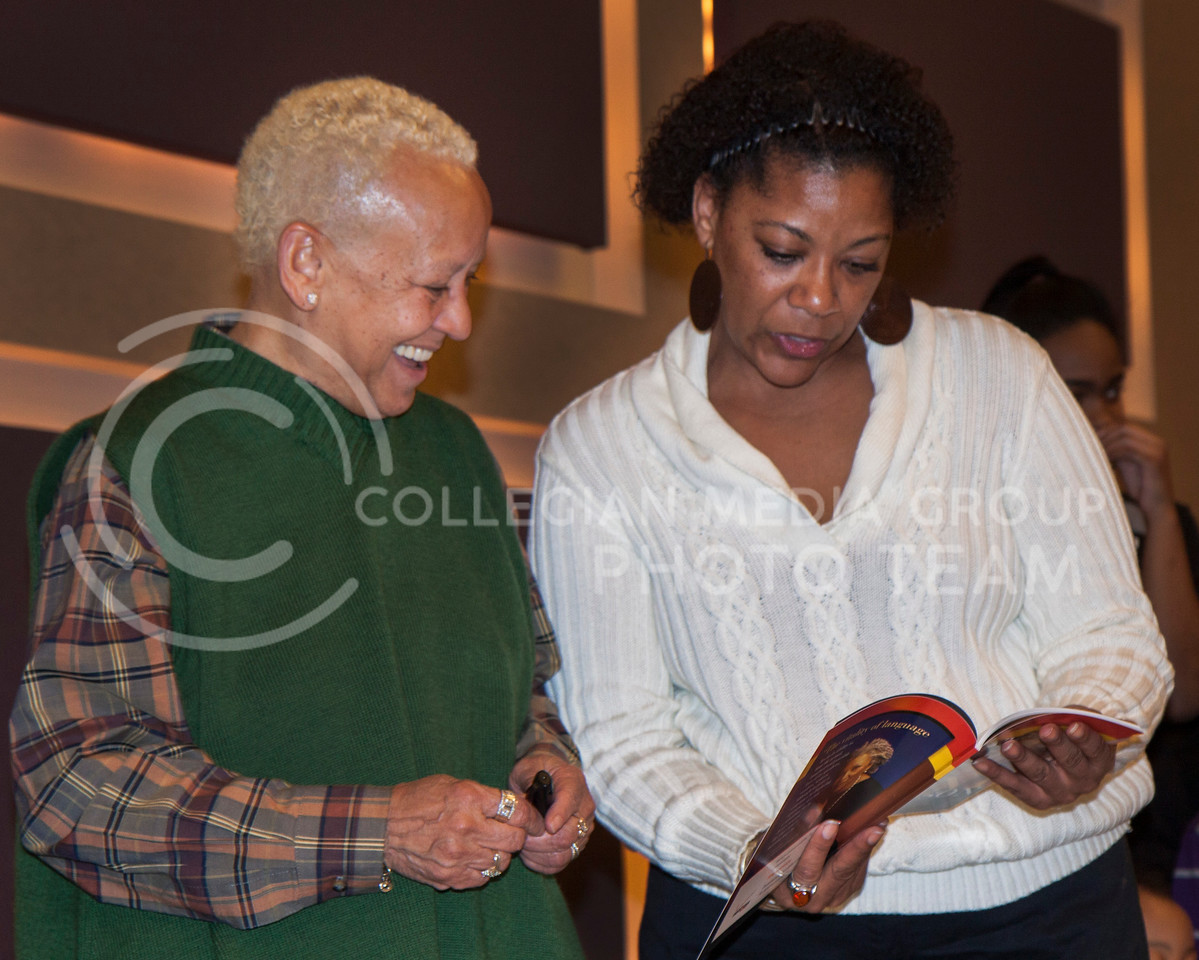 (Photo by Landry Mastellar | Collegian)<br /> <br /> Nikki Giovanni admires the free book she passed out February 6, 2013 evening at the Alumni Center with a guest of the event. Giovanni Is a well known award winning poet and human rights activist. The event was hosted by the BSU.