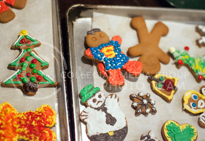 Gingerbread cookies decorated in different ways line cookie sheets on a tabel in The Chef breakfest cafe Tuesday night. Besides snow men, Christmas trees, and Superman, other decorations included a Fiesta Bowl themed star, Bill Snyder, and an LGBT themed star.  (Photo by Evert Nelson / Collegian)