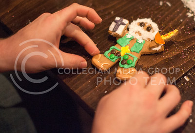 The hands of Caleb Wasinger, Manhattan resident, makes adjustment to his gingerbread man Tuesday night at The Chef. Not a normal time for the cafe to be open, Owners Kevin and Kurstian Harris, Manhattan residents, invited employees and friends to help decorate gingerbread cookies for their tree.  (Photo by Evert Nelson / Collegian)