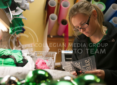 Cutting printed designs, Emily Williamson, freshman studying accounting, works hard at Threads Wednesday night making t-shirts with Fake Patty's Day themes on them. Williamson has been working at Threads since last October.  (Photo by Evert Nelson | Collegian)