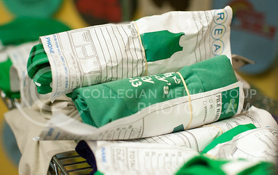 Shirts wrapped up in order forms lay on a rack in Threads Wednesday night. The mass of green shirts are mainly for Saturday's Fake Patty's Day event.  (Photo by Evert Nelson | Collegian)