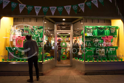 A person peaks in to Threads in Aggieville Wednesday night while customers look at the various green shirts inside. Aggieville has been prepping for Fake Patty's Day by making printed shirts for those who want them.   (Photo by Evert Nelson | Collegian)