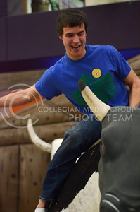 (Photo by Parker Robb | Collegian)  Daniel Preston, sophomore in milling science, holds on for dear life as to not get thrown from the fake bull at the UPC After Hours Western Night at the K-State Student Union Friday night.