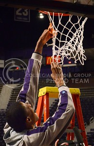 (Parker Robb | Collegian)  Senior center Jordan Henriquez cuts down his portion of the net without the help of a ladder during the pep rally March 11 at Bramlage Coliseum. The Big XII trophy returns to Manhattan for the first time since 1977.