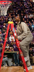 (Photos by: Emily DeShazer | Collegian) DJ Johnson climbs the ladder to take the first cut to bring down the net at Bramlage Coliseum on March 11, 2012 after winning a share of the Big 12 championship.