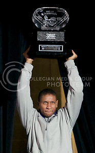 (Photo by Jed Barker | Collegian) Senior guard, Rodney McGruder walks out from behind the curtain, holding high the Big 12 Men's Basketball trophy during the K-State Big 12 title celebration at Bramlage Coliseum on March 11, 2013.