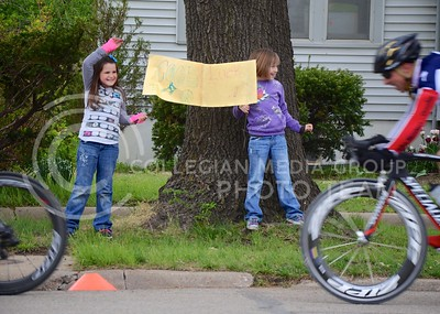 (Photo by Parker Robb | Collegian)  Two girls wave and hold a handmade sign wishing the cyclists good luck during one of the criterium races of the Tallgrass Classic, held May 5, 2013, on a lap course around City Park. Collegiate and semi-pro cyclists came from many different states to compete in this event, which also included a road race by Tuttle Creek Lake the previous day.