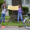 (Photo by Parker Robb | Collegian)<br /> <br /> Two girls wave and hold a handmade sign wishing the cyclists good luck during one of the criterium races of the Tallgrass Classic, held May 5, 2013, on a lap course around City Park. Collegiate and semi-pro cyclists came from many different states to compete in this event, which also included a road race by Tuttle Creek Lake the previous day.