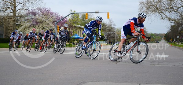 (Photo by Parker Robb | Collegian)  Cyclists whiz around a corner at 11th and Poyntz Avenue during one of the criterium races of the Tallgrass Classic, held May 5, 2013, on a lap course around City Park. Collegiate and semi-pro cyclists came from many different states to compete in this event, which also included a road race by Tuttle Creek Lake the previous day.
