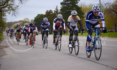 (Photo by Parker Robb   Collegian)  Cyclists, jockeying for position, fly down Poyntz Avenue during one of the criterium races of the Tallgrass Classic, held May 5, 2013, on a lap course around City Park. Collegiate and semi-pro cyclists came from many different states to compete in this event, which also included a road race by Tuttle Creek Lake the previous day.