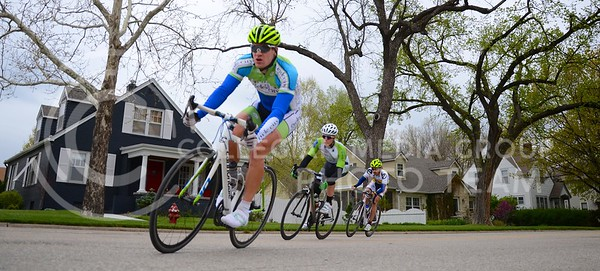 (Photo by Parker Robb | Collegian)  Cyclists pass in front of houses on 14th Street during one of the criterium races of the Tallgrass Classic, held Sunday on a lap course around City Park. Collegiate and semi-pro cyclists came from many different states to compete in this event, which also included a road race by Tuttle Creek Lake the previous day.