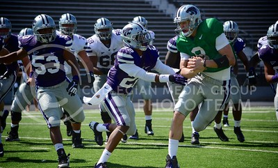 (Photo by Parker Robb | Collegian)  Freshman quarterback Joe Hubener attempts to advance the ball past sophomore defensive back Dante Barnett during the annual Purple-White Spring Game April 27, 2013, at Bill Snyder Family Stadium.