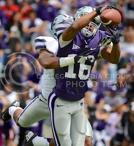 (Photo by Parker Robb | Collegian)  Junior wide receiver Tyler Lockett hauls in a catch while being tackled by defensive back Carl Miles, Jr., during the annual Purple-White Spring Game April 27, 2013, at Bill Snyder Family Stadium.