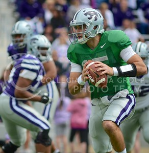 (Photo by Parker Robb | Collegian)  Junior quarterback Jake Waters looks downfield for an open receiver as he is flushed out of the pocket during the annual Purple-White Spring Game April 27, 2013, at Bill Snyder Family Stadium.