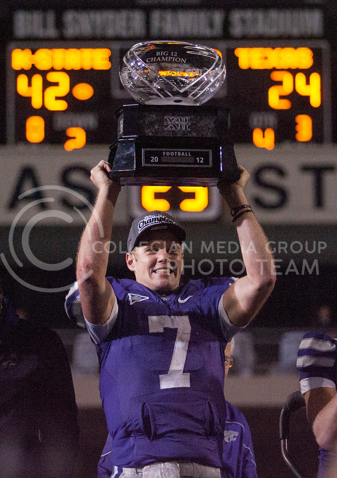 Senior quarterback Collin Klein holds up the Big XII trophy after receiving it at a ceremony after the Cats victory over the Longhorns at Bill Snyder Family Stadium.<br /> <br /> (Photo by Evert Nelson / Collegian)