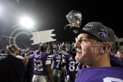 #83 Logan Stephens, junior wide receiver, smiles and holds his helmat up while the Wildcats are awarded the Big XII Champion trophy after their victory against Texas Satuday at Bill Snyder Family Stadium.  (Photo by Evert Nelson / Collegian)