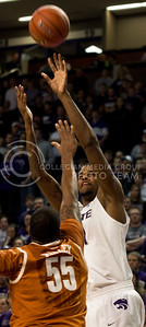 Senior forward Jordan Henriquez jumps over University of Texas freshman center Cameron Ridley during the Wildcats' 83-57 victory over the visiting Longhorns on January 30th in Bramlage Coliseum. [Jacob Dean Wilson]