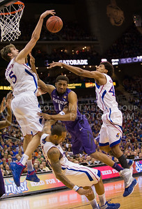 [Photo by Emily DeShazer | Collegian] Jeff Whithey blocks Shane Southwell's shot as Travis Releford falls to the ground during the title game of the Big 12 Championship at the Sprint Center on March 16, 2013.