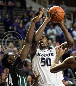 Freshman forward D.J. Johnson jumps above University of South Carolina-Upstate junior forward Babatunde Olumuyiwa for a shot during the Wildcats' 72-53 victory over the visiting Spartans on December 2nd in Bramlage Coliseum. [Jacob Dean Wilson]