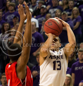 (Photo by Jacob Dean Wilson | Collegian) Sophomore guard Angel Rodriguez jumps over an opposing Lamar defender for a 3-pointer during the Wildcats' 79-55 win against the visiting Cardinals on Nov. 12, 2013 in Bramlage Coliseum. The game was part of the NIT Season Tip-Off Midwest Regional. Rodriguez finished with a game-high 19 points, shooting 4-of-6 from the 3-point line.