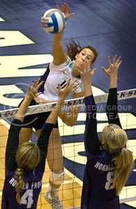 Junior outside hitter Courtney Traxson spikes the ball against TCU's senior middle blocker Emily Kirby and sophomore right side hitter Stephanie Holand during the Wildcats' three-set sweep against the visiting Horned Frogs on November 10th in Ahearn Field House. Traxson finished the match with 7 kills. [Jacob Dean Wilson]