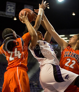 Senior guard Mariah White attempts a shot over the outreaching hands of Illinois senior guard Adrienne GodBold and sophomore guard Ivory Crawford during the Wildcats' 66-48 win over the visiting Fighting Illini on March 30, 2013 in Bramlage Coliseum during the Quarterfinals of the Women's National Invitation Tournament (WNIT). With the victory, the Wildcats' advance to the WNIT Semifinals and are set to face Utah on April 3rd in Bramlage Coliseum. [Jacob Dean Wilson | Collegian]