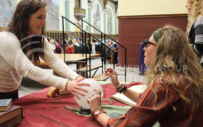 Josh Staab // The Collegian  Courtney Liebl, Junior in Journalism, smiles as she receives her winning lottery numbers from the Divination expert, Proffesor Trelawney.  Lyndi Stucky, or Professor Trelawney read peoples fortunes and even predicted that one of the members of the feast will die within the month during last night's Back to School Harry Potter Event in the Great Room.