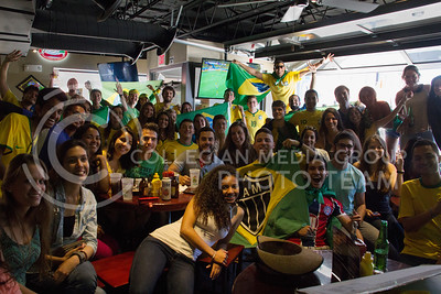 (Photo by Taylor Alderman | Collegian)  Brazil fans pose for a picture during a World Cup watch party at Tanner's Bar and Girl on June 12, 2014.