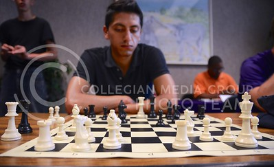 (Photo by Parker Robb | Collegian)  Andres Peralta, a student from Ecuador in the Go-Teacher program, ponders his next move as former New Zealand national chess champion Jonathan Sarfati makes his way around the room filled with chess boards August 26 at the Chess Challenge, hosted by the Creation Club at the K-State Student Union.