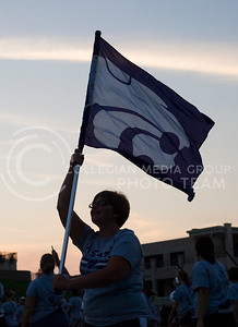 A color guard member waves a powercat flag over the field Sunday at Bill Snyder Family Stadium.  The Pride of Wildcat Land performed as students from all over learned the moves to game song staples like the Wabash Cannonball. (Photo by Emily DeShazer / The Collegian)