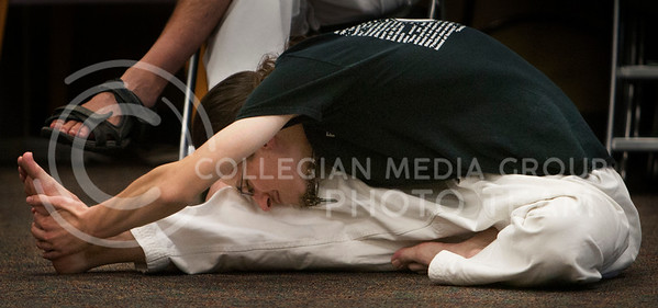 Michael Halliwell, 3rd degree black belt from Sun Yi's Academy of Tae-Kwon-Do stretches out for Wednesday nights self defense event held at Jardines' Frith Community Center. This event was held to support community and self defense awareness amongst the students who live in the LLC. (Photo by Zachary Werhan / The Collegian)