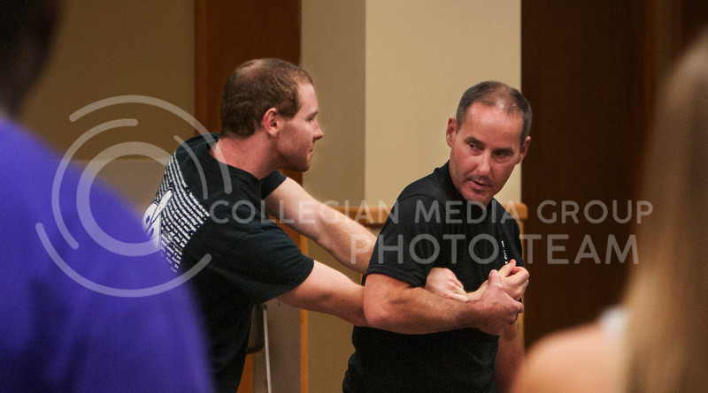 Master David Moore (right), sixth degree black belt from Sun Yi's Academy of Tae-Kwon-Do demonstrates on partner how to show students self defense tactics at the Jardine Frith Community Center on Wednesday evening. About fifteen residents from Jardine attended the class. (Photo by Zachary Werhan / The Collegian)