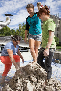 Amy Santoferraro (left), a ceramics area coordinator and assistant professor of arts, and Lisa Allen (right), a senior majoring in life science and ceramics, help Julia Polidoro (middle), a senior in ceramics, ascend the mound of clay.  The second annual Clay Stomp was held Saturday, Sept. 28, 2013 from 10am to 3pm outside of Willard Hall. All K-students were welcome to come with their barefeet to mix 4,000 pounds of clay, which would later be bagged and used by art students.