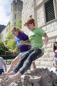 "Lauren Karle, a third year graduate student in ceramics, and Lisa Allen, a senior majoring in life science and ceramics, perform a ""buttbomb"" on the clay.  The second annual Clay Stomp was held Saturday, Sept. 28, 2013 from 10am to 3pm outside of Willard Hall. All K-students were welcome to come with their barefeet to mix 4,000 pounds of clay, which would later be bagged and used by art students."