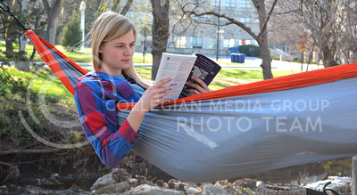 (Photo by George Walker | Collegian)   Elizabeth Bittiker, freshman in social work, reads The Mi'Kmaq while relaxing in her hammock in the Quinlan Natural Area yesterday afternoon.
