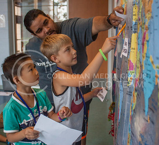 Photo by Erin Poppe | the collegian Gaston Aulestia, an ecuadorian in the Go Teacher program, assists second graders Tyrus Moore and Liyang Tan in labeling U.S. regions Tuesday at the Boys and Girls Club of Manhattan's Fifth Street site.