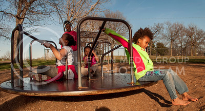 from right: Isis Roberts, 9, Lluvia Beverly, 5, and Daija Roberts, 7, hang onto the spinning merry-go-round in Cico Park on Tuesday afternoon.