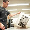 (Photo by Parker Robb | Collegian)  Marco Hernandez, graduate student in printmaking, pulls an etching, engraving and aquatint print off the printing plate after running it through the press February 12, 2014, in Willard Hall. His piece is based on Mexican culture, including the iconic eagle and snake found on the Mexican flag, a cactus and a skeleton with a sickle from the Mexican card game Lotería, and overall depicts the escalating crime in northern Mexico due to drug cartels.
