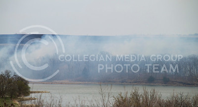 (Photo by Taylor Alderman | Collegian)  The wind blows the smoke over Pottawatomie Lake #2 as farmers burn away weeds to refreshen the land on April 10th, 2014.
