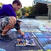 "(Photo by Parker Robb | Collegian)  Nate Baranowski, owner of Street Canvas Design based out of Tampa Bay, Florida, draws in details on his sidewalk art October 10, 2013 in Bosco Plaza.  The three-dimensional sidewalk piece promotes the Union Program Council's ""Week of Science"" events and their slogan ""Events down to a science."""