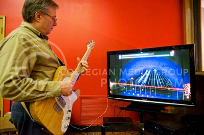 (Photo by Parker Robb | Collegian)  Kurt Gartner, associate director of the School of Music, Theatre and Dance at K-State, learns to play a riff from a rock song using Rocksmith 2014 January 30, 2014, at Manhattan Christian College. Though it looks similar to games like Guitar Hero and Rockband, musicians can plug their real guitars into Rocksmith and use its lessons and training exercises to learn to play their instrument, much like Rosetta Stone uses immersion to teach language.
