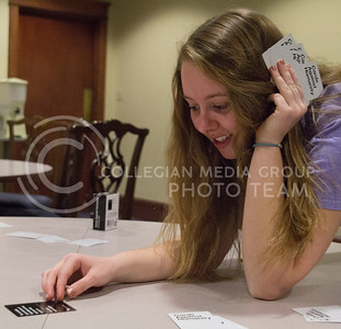 (Photo by Taylor Alderman | Collegian)  Madison Randall, sophomore in hospitality management, reads the black card to decide which white card to play in the game Cards Against Humanity on February 13, 2014. Cards Against Humanity is an adult version of the game, Apples to Apples.